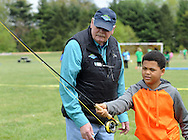 Bob Powell, of Clementon, New Jersey and an L.L. Bean fly fishing expert shows Jonathan Leath Jr, 11 of Moorestown, New Jersey how to cast a line during YMCA 'Healthy Kids Day'  Saturday April 30, 2016 in Mt. Laurel, New Jersey.  (Photo by William Thomas Cain)