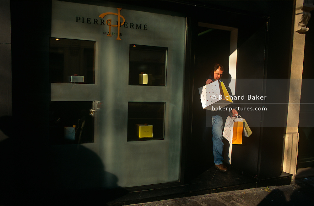 A shopper laden with shopping bags emerges from the Paris chocolatier shop Pierre Hermé on Rue Vaugirard.