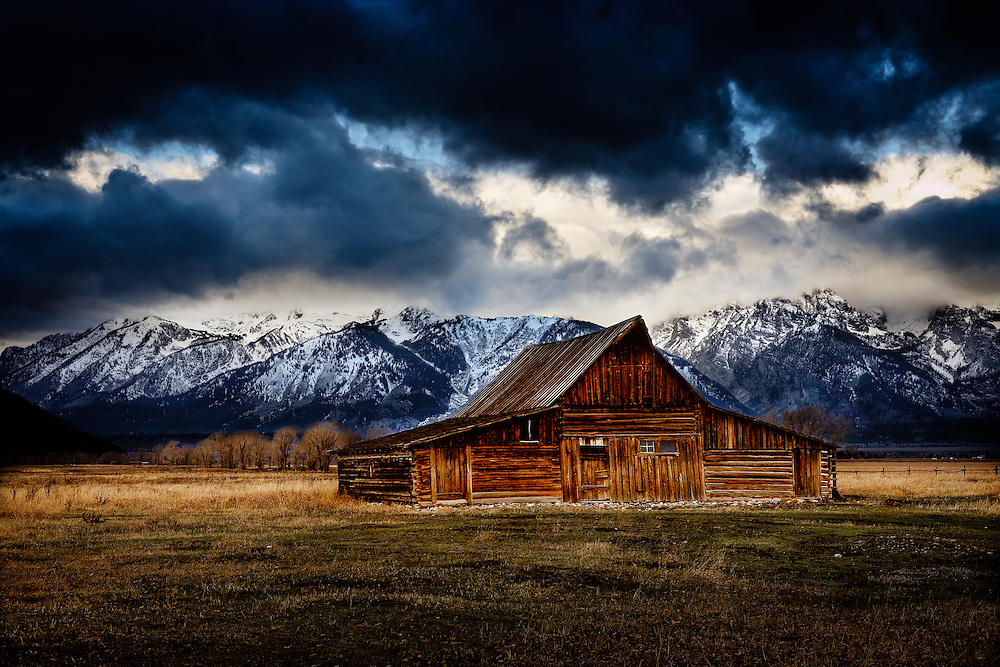 Moulton barn in late fall with early snowfall covering the peaks of the Tetons in the distance.