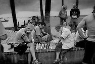 Middle-aged western men playing chess on the seafront promenade where hundreds of young female sex workers gather at all times of the day.   Although not all foreign men come to Pattaya for the sex industry, there are vast numbers of foreign middle-aged men who are attracted to Pattaya feeding this industry.  Thailand.