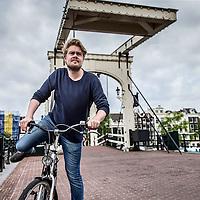 Nederland, Amsterdam, 10 juli 2016.<br /> Jorrit Kleijnen van HAEVN.<br /> Haevn is een Nederlands electrodance-popduo, door popkenners eind 2015 bestempeld als één van de poptalenten voor 2016. De band bestaat uit (film)componist Jorrit Kleijnen en zanger/singer-songwriter Marijn van der Meer<br /> Op de foto: Jorrit fietsend vanuit zijn studio naar huis over de Magere brug vlakbij Carré.<br /> <br /> <br /> Foto: Jean-Pierre Jans