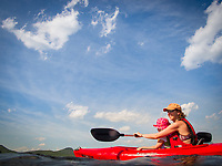 A mother and young daughter enjoy a tranquil paddle on a Vermont pond in summer.