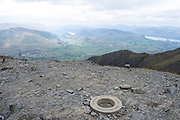 The Trig Point, a concrete ring, at the highest point, Hallsfell spur, of Blencathra Mountain, Lake Districts, Cumbria, UK.  Trig Points are the common name for Triangulation Pillars  are used by Ordnance Survey to determine the exact shape of the country by creating direct line of sight to another Trig Point.  The beautiful hills and valleys of the Lake District National Park surrounds the mountain. The sky is cloudy and overcast. (photo by Andrew Aitchison / In pictures via Getty Images)