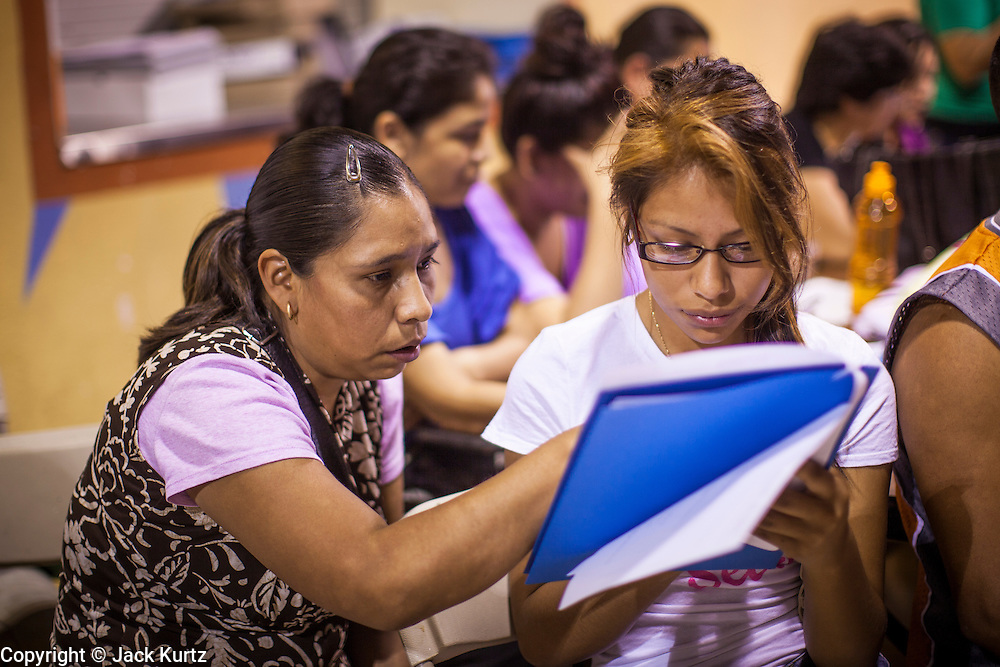 """18 AUGUST 2012 - PHOENIX, AZ:    PHOTO BY JACK KURTZ18 AUGUST 2012 - PHOENIX, AZ:  A woman and her daughter go over the paper required to apply for the """"deferred action"""" program during a deferred action workshop in Phoenix. More than 1000 people attended a series of 90 minute workshops in Phoenix Saturday on the """"deferred action"""" announced by President Obama in June. Under the plan, young people brought to the US without papers, would under certain circumstances, not be subject to deportation. The plan mirrors some aspects the DREAM Act (acronym for Development, Relief, and Education for Alien Minors), that immigration advocates have sought for years. The workshops were sponsored by No DREAM Deferred Coalition.  PHOTO BY JACK KURTZ"""