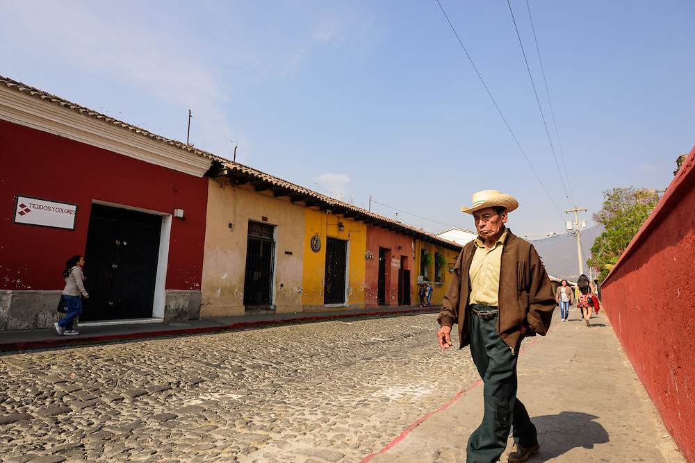 Man with a hat walking the colorful streets of Antigua, Guatemala.