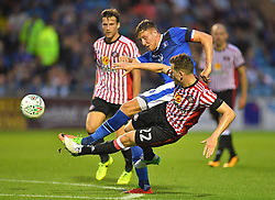Carlisle United's Richard Bennett gets a shot off despite the attentions of Sunderland's Donald Love