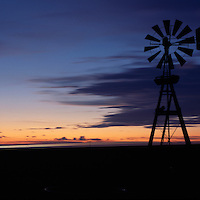 Canada, Saskatchewan, Tompkins, Windmill along lights of Trans-Canada Highway on autumn evening