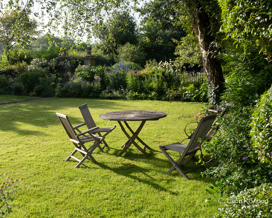 Teak garden furniture on a lawn surrounded by herbaceous borders at Lower Severalls Farmhouse,  Crewkerne, Somerset, UK