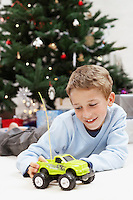 Little Boy Playing with Toy Truck by christmas tree