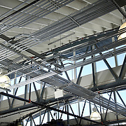 Silvery, well-lit runs of electrical conduit in the ceiling of medium size factory..