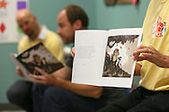 """Pearson's Teresa Flack (right) holds up a copy of """"Otis"""" by Loren Long as it is read to the class by Kerry Wegman during Jumpstart's Read for the Record event at Waypoint Uptown Kids Child Development Center in Cedar Rapids on Thursday, October 3, 2013. Jumpstart's Read for the Record in partnership with the Pearson Foundation is a world-record-breaking campaign that brings together children and adults to read the same book on the same day. 73 Pearson employees from their Iowa City location visited 34 schools and daycares in Cedar Rapids, Iowa City, and the surrounding area as part of the program."""