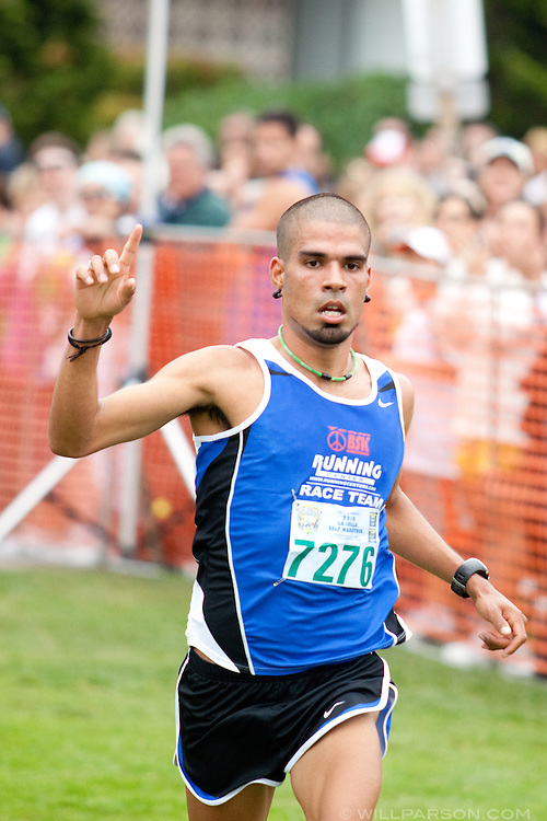 Sergio Gonzalez from Oceanside crosses the finish line in first place with a time of 1:09:48 during the La Jolla Half Marathon, April 25, 2010.