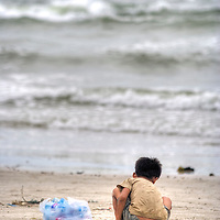 Boy stands on beach, Sihanoukville, Cambodia