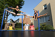 8/5/14 5:48:41 PM -- Bethesda, MD, U.S.A  -- Gymnastics family for concussion story --     Anastasia, 12, left, and Aleka Frazier, 10, bounce on their trampoline at their home as parents Sean and Marie watch.  Photo by H. Darr Beiser, USA TODAY Staff ORG XMIT:  HB 131472 CONCUSSION 08/05/2014 (Via OlyDrop)