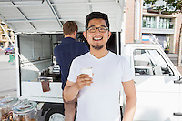 Portrait of customer holding disposable coffee cup against vendor and mobile shop