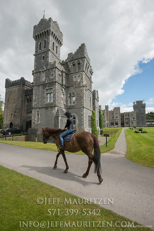 A woman rides a horse past Ashford Castle, a 13th century castle turned into a 5 star luxury hotel.