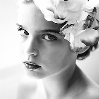 A young girl looking at camera with flowers in hair