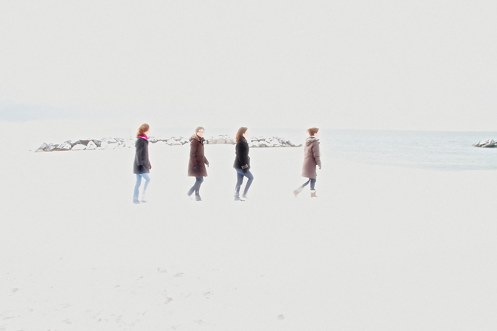 Four sisters walk along a Lake Ontario beach in the Beaches neighbourhood of Toronto, Canada