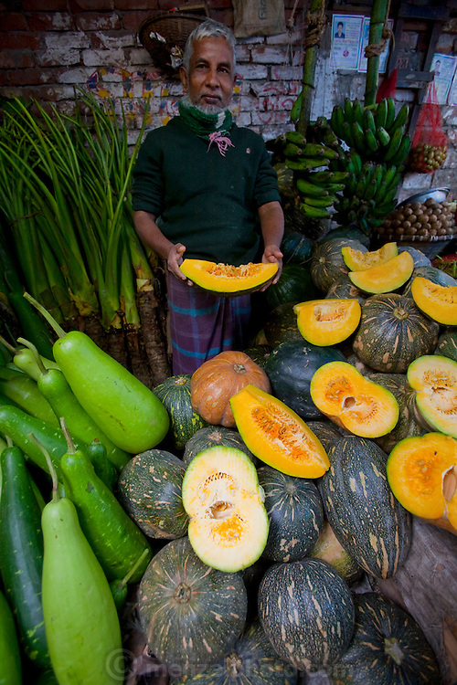 A vendor displays pumpkins and squash at his market stall at the Santinagar  market in Dhaka, Bangladesh.