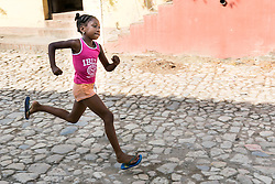 Girl running on cobblestone street in UNESCO world heritage site of Trinidad, Cuba.