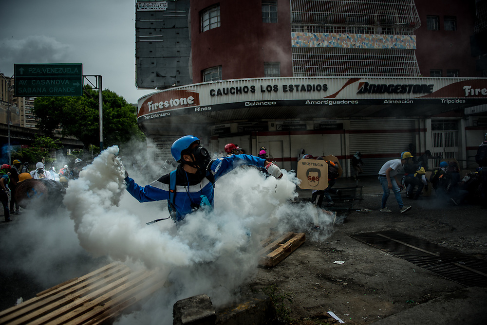 CARACAS, VENEZUELA - MAY 22, 2017:  Anti-government protesters use homemade shields and hurl stones and molotov cocktails during clashes with security forces, who responded by heavily tear gassing and firing rubber bullets and buckshot at them. The streets of Caracas and other cities across Venezuela have been filled with tens of thousands of demonstrators for nearly 100 days of massive protests, held since April 1st. Protesters are enraged at the government for becoming an increasingly repressive, authoritarian regime that has delayed elections, used armed government loyalist to threaten dissidents, called for the Constitution to be re-written to favor them, jailed and tortured protesters and members of the political opposition, and whose corruption and failed economic policy has caused the current economic crisis that has led to widespread food and medicine shortages across the country.  Independent local media report nearly 100 people have been killed during protests and protest-related riots and looting.  The government currently only officially reports 75 deaths.  Over 2,000 people have been injured, and over 3,000 protesters have been detained by authorities.  PHOTO: Meridith Kohut