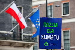 London, UK. 1st December, 2018. A placard bearing a message in Polish is held by environmental campaigners outside the Polish embassy during a Together for Climate Justice demonstration in protest against Government policies in relation to climate change, including Heathrow expansion and fracking. Following a rally outside the Polish embassy, chosen to highlight the UN's Katowice Climate Change Conference which begins tomorrow, protesters marched to Downing Street.