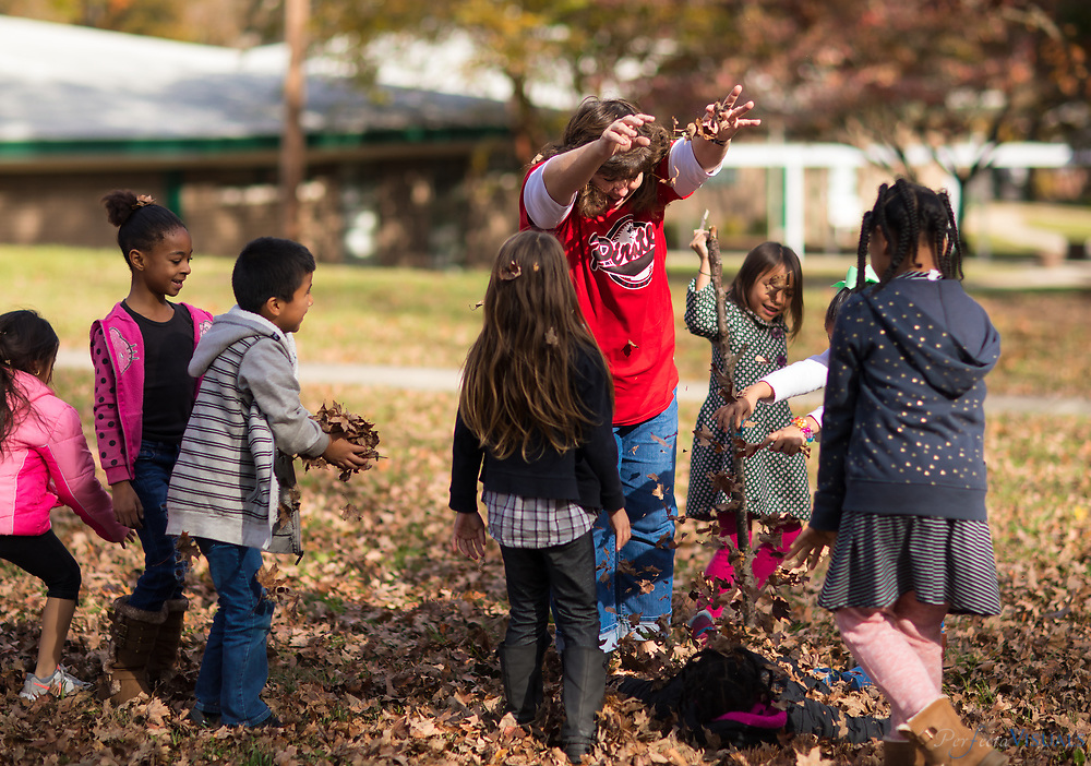 First grade teacher, Debbie Lake, has a brief leaf fight with her students on the lawn of Irving Park Elementary.<br /> <br /> Photographed, Friday, November 17, 2017, in Greensboro, N.C. JERRY WOLFORD and SCOTT MUTHERSBAUGH / Perfecta Visuals