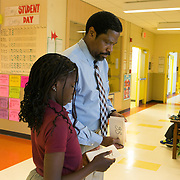 WASHINGTON, DC - APR 24:  Tyrone Pittman, dean of students at Simon Elementary School in Washington, DC, greets arriving students, April 24, 2014, while fifth grader Tonyia Cheadle, passes out numbered index cards to each arriving student. The cards become a raffle ticket for the daily raffle held in the cafeteria. DC has enormous truancy rates, even among young children. In the last year or two, the school system has made a big push to improve attendance. Simon Elementary is seen as a model, introducing incentives and games that are tied to attendance and meant to get kids excited about coming to school; systems to ensure that parents get a call home whenever their kids are absent; weekly attendance meetings to talk about kids who are missing too much school; and a partnership with a community based organisation that can make home visits and connect families with services. (Photo by Evelyn Hockstein/For The Washington Post)