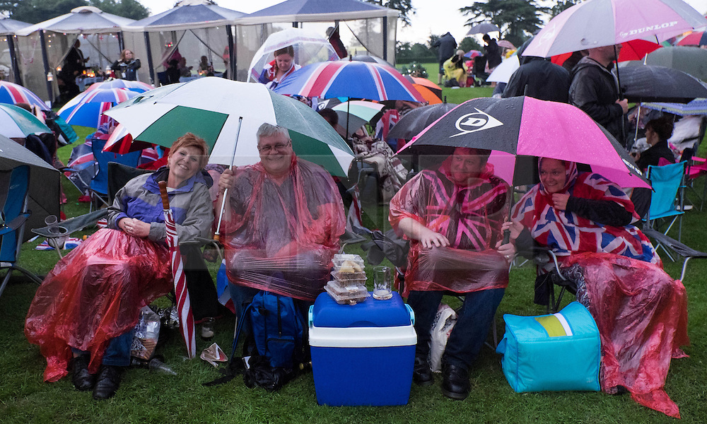 © Licensed to London News Pictures.22/08/15<br /> Castle Howard, North Yorkshire, UK. <br /> <br /> Friends huddle under umbrellas as a thunder storm brings heavy rain during the  25th anniversary of the Castle Howard Proms event near York. The theme of the event this year is a commemoration of the 75th anniversary of the Battle of Britain and the 70th anniversary of VE day and brings an evening of classic musical favourites celebrating Britishness to the lawns of Castle Howard.<br /> <br /> Photo credit : Ian Forsyth/LNP