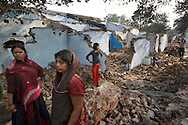 Residents of Angarpathra village in Dhanbad, Jharkhand, India stand on Dec 5, 2014 on rubble where their houses once stood. Forty five houses in the village collapsed as the earth caved in due to an underground coal fire on Nov 14. The residents blame the government for not taking any action to divert the fire because it wants to evict villagers from the mining site.   <br /> (Photo by Kuni Takahashi)