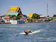 "28 OCTOBER 2014 - BANGKOK, THAILAND: A ""long tailed"" boat, used as taxis on the Chao Phraya River, goes down the river past Wat Kanlaya in the Thonburi section of Bangkok.    PHOTO BY JACK KURTZ"