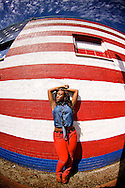 Young lady standing against a wall in Deep Ellum painted as the American Flag with the blue sky and clouds above.