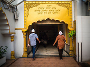"08 FEBRUARY 2015  BANGKOK, THAILAND: People walk in the Sikh temple in Bangkok. Thailand has a small but influential Sikh community. Sikhs started coming to Thailand, then Siam, in the 1890s. There are now several thousand Thai-Indian Sikh families. The Sikh temple in Bangkok, Gurdwara Siri Guru Singh Sabha, was established in 1913. The current building, adjacent to the original Gurdwara (""Gateway to the Guru""), was built in 1979. The Sikh community serves a daily free vegetarian meal at the Gurdwara that is available to people of any faith and background.     PHOTO BY JACK KURTZ"