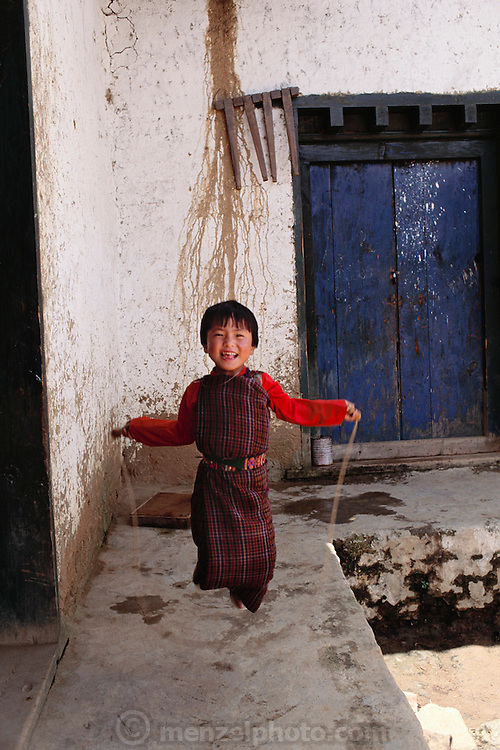 Little girl plays jump rope in front of her rammed earth home in the village of Gaselo, Bhutan. From Peter Menzel's Material World Project.