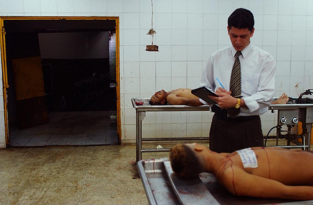 Inspector Jose Rangel of the Cuerpo de Investigaciones Cientificas, Penales y Criminales(CICPC) takes notes on two homicide victims in the morgue.  The CICPC is a national organization whose Homicide division investigates murders in Venezuela.