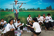 "04 FEBRUARY 2013 - PHNOM PENH, CAMBODIA:   Cambodians sit next to a billboard of a farmer while they rest on their way to the cremation of King-Father Norodom Sihanouk in Phnom Penh. Norodom Sihanouk (31 October 1922 - 15 October 2012) was the King of Cambodia from 1941 to 1955 and again from 1993 to 2004. He was the effective ruler of Cambodia from 1953 to 1970. After his second abdication in 2004, he was given the honorific of ""The King-Father of Cambodia."" Sihanouk died in Beijing, China, where he was receiving medical care, on Oct. 15, 2012.  PHOTO BY JACK KURTZ"