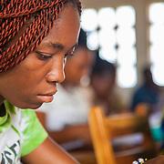 LÉGENDE: BTS génie civil 1ère année mécanique. Pendant la correction du devoir surveillé de mécanique et remises des copies aux étudiants. LIEU: CERFER, Lomé, Togo. PERSONNE(S): Portrait d'une étudiante en pleine concentration sur son devoir.