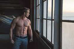 man with an incredible body standing near a large window in a parking garage