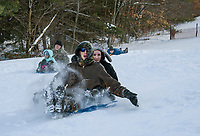Autumn Boisvert with Ernie Boisvert, Caleb Cox with Naomi Stebbins and Justin Cox race each other down the sledding hill at Gilford Outing Club on Tuesday afternoon.  (Karen Bobotas/for the Laconia Daily Sun)