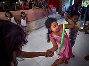 26 JANUARY 2017 - MALILIPOT, ALBAY, PHILIPPINES: Children who live on the slopes of the Mayon volcano play games organized by Philippine Red Cross in a shelter in Malilipot. The volcano was relatively quiet Friday, but the number of evacuees swelled to nearly 80,000 as people left the side of  the volcano in search of safety. There are nearly 12,000 evacuees in Santo Domingo, one of the communities most impacted by the volcano. The number of evacuees is impacting the availability of shelter space.    PHOTO BY JACK KURTZ