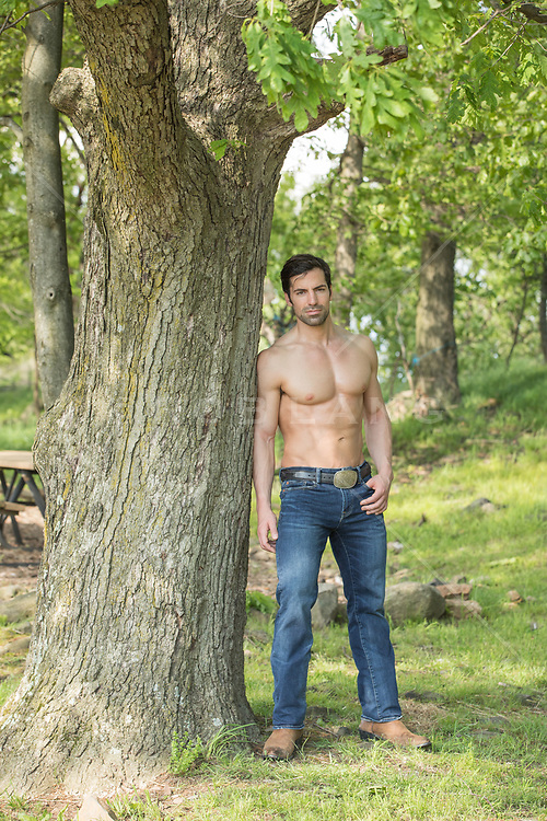 shirtless muscular man with smooth skin leaning against a tree