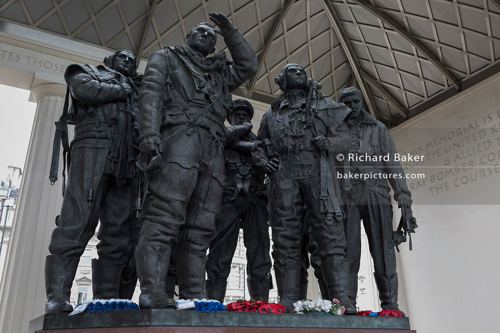 The sculpture forming the Bomber Command War Memorial on 16th March 2017, in Green Park, London, England. The 9-foot (2.7 m) bronze sculpture of seven aircrew, designed by the sculptor Philip Jackson look as though they have just returned from a bombing mission and left their aircraft. The figures represent L-R: Navigator, Flight Engineer, Mid-upper gunner, Pilot, Bomb aimer, Rear gunner and Wireless operator. The Royal Air Force Bomber Command Memorial is a memorial in Green Park, London, commemorating the crews of RAF Bomber Command who embarked on missions during the Second World War. The memorial was built to mark the sacrifice of 55,573 aircrew from Britain, Canada, Czechoslovakia, Poland and other countries of the Commonwealth, as well as civilians of all nations killed during raids. Queen Elizabeth II unveiled the memorial on 28 June 2012, the year of her Diamond Jubilee.