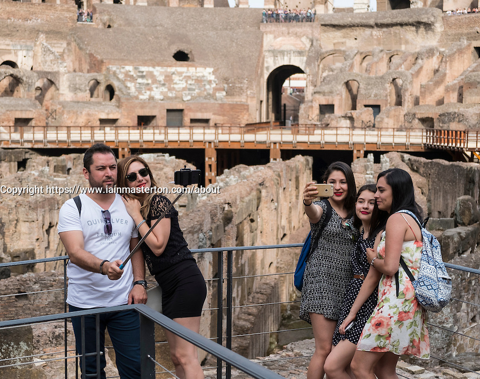Tourists taking selfie photographs at the Colosseum in Rome Italy