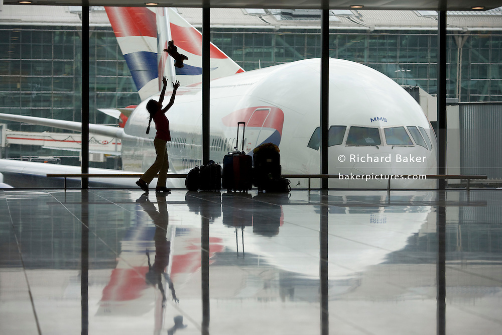 "A young girl in transit between India and the US, entertains herself by throwing her pet toy tiger as far as the ceiling in a departure window of Heathrow Airport's Terminal 5. In front of a Boeing 777 jet airliner's nose and cockpit, the girl is a silhouette against the large windows that allow in the natural light. Behind the parked aircraft, another British Airways passenger jet taxies past, its tail at right-angles to the stationary airplane although they both look like the same plane. With her family baggage next to her, the child is enjoying some hours of freedom before another long-haul flight westwards. From writer Alain de Botton's book project ""A Week at the Airport: A Heathrow Diary"" (2009)."