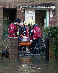 © London News Pictures. 12/02/2014. Egham, UK.  An elderly man being evacuated from his home in s stretcher by members of a fire and rescue team in Egham in Surrey. Torrential rain in the area is due to raise water levels increasing the risk of further flooding. Photo credit : Ben Cawthra/LNP
