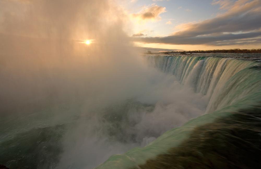 Dramatic sunrise through mist Horseshoe Falls Niagara Falls Canada