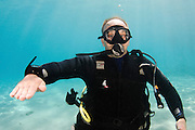 Underwater Hand signs scuba diver demonstrates the sign language for divers. Level off at this depth: Flat hand with palm down and fingers spread moved slowly back and forth horizontally.