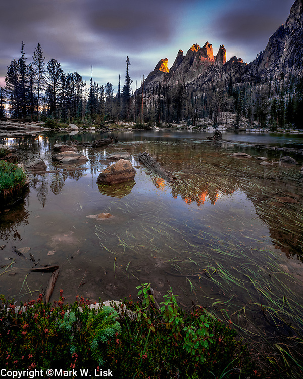 War Bonnet peaks reflects into the waters of Feather Lakes. Sawtooth Wilderness Area, Idaho.