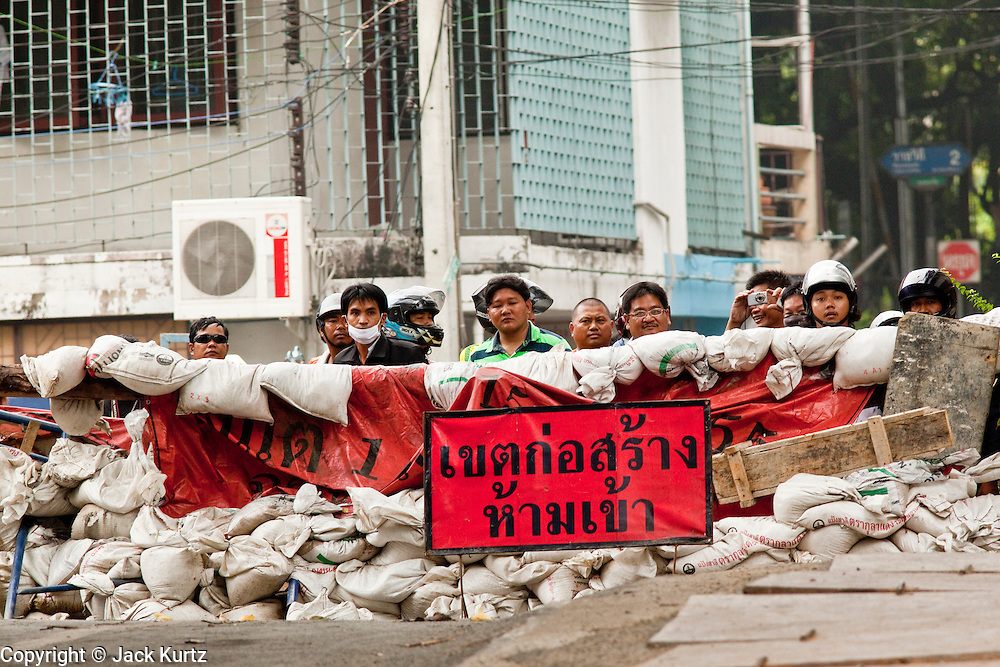 18 MAY 2010 - BANGKOK, THAILAND: Thai civilians watch men build barricades from the safety of their own barricade at Din Daeng Intersection in Bangkok Tuesday. The intersection has been under periodic sniper fire from unidentified snipers near Thai military lines. Violent unrest continued in Bangkok again Tuesday nearly a week after Thai troops started firing on protesters and Bangkok residents took to the streets in violent protest against the government. Tuesday was not as violent as previous days however. Although protesters continued to set up roadblocks and flaming tire barricades across parts of the city, there was not as much gunfire from the government lines. The most active protesters were at the Din Daeng Intersection about a mile from the Red Shirts' Ratchaprasong camp.  PHOTO BY JACK KURTZ
