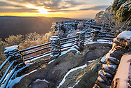 The sun sets over the snow and ice covered barricades that surround Coopers Rock in Morgantown, West Virginia.